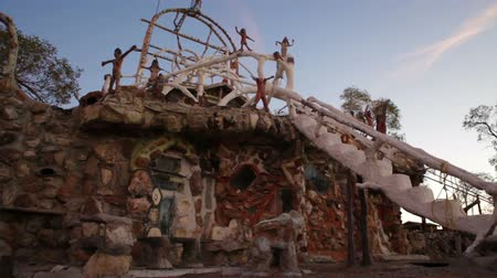 zajímavý : Dolly shot showing the front of the eclectic building at Thunder Mountain Park in Imlay, Nevada. There is a white staircase and statues on the roof.