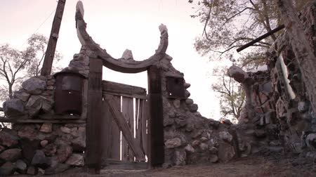 zajímavý : Dolly shot showing the wooden gate and rundown stone walls at Thunder Mountain Park in Imlay, Nevada. There is a semi-circular sculpture above the gate.