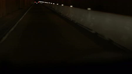 mroczne : Driving down a dark highway at night. Only able to see reflectors on road barrier and taillights of car ahead. California. Wideo