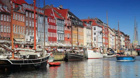 kodaň : Static shot of colorful buildings and people on street and ferry boat on a river at Copenhagen, Denmark