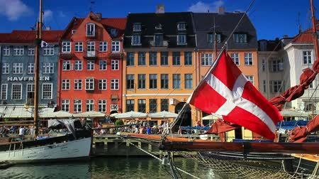 kodaň : Static shot of old buildings with Danish flag mounted on a boat in the foreground. The shot was taken in Copenhagen, Denmark. Dostupné videozáznamy