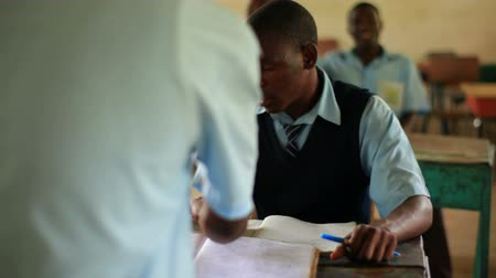 aluna : Shot of school boy doing homework in class, girl comes and sits by him, in Kenya, Africa. Vídeos
