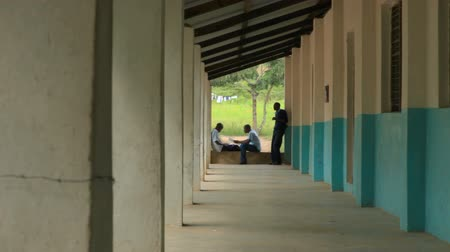 kmenový : Shot of 2 school boys studying, and one boy standing nearby, in an outside hallway in a school in Kenya, Africa. Dostupné videozáznamy