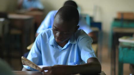 czarne : Shot of a school boy reading his book in class in Kenya, Africa.