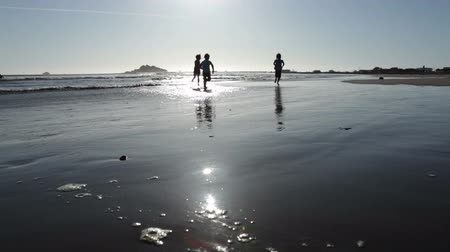 pegadas : Low stationary then pan of three girls running away from shot on wet sand on beach left by waves. California.