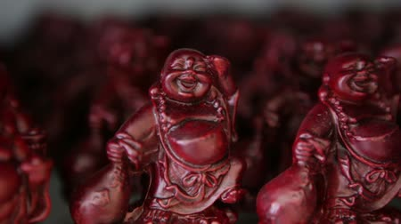philosopher : Steady shot of a shelf of small Buddha figurines in a gift shop. California