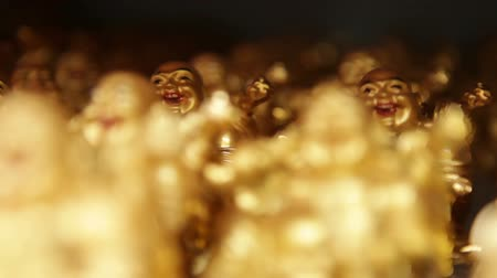 philosopher : Moving shot of small golden Buddha figurines on a gift shop display shelf. California