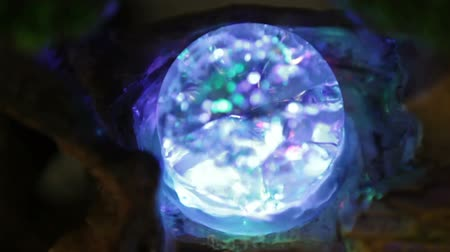 bolas : Spinning crystal ball with colorful lights. It spins in water as part of a statue.