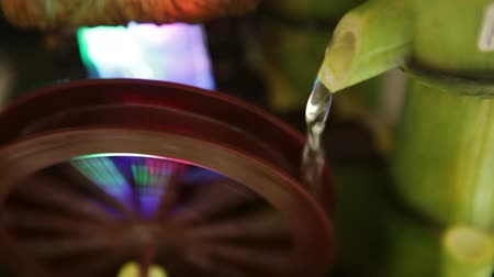 młyn : Steady shot of a waterwheel fountain fed by a bamboo waterfall. California Wideo