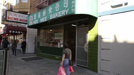 kínai negyed : Steady shot as people walk past a bakery in Chinatown. California