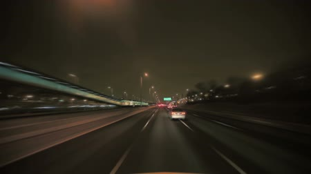 converge : Shot a vehicle traveling on the interstate at night in Chicago in traffic. Stock Footage
