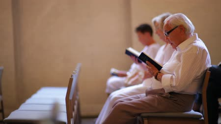 christian : Dolly shot of elderly people reading the bible at a church in Copenhagen, Denmark.