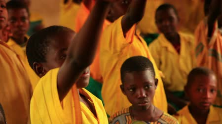 placa : Close up of boy raising his hand in a full classroom in Kenya, Africa. Front view.
