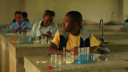 microbiologia : School boy doing chemistry in Kenya, Africa.