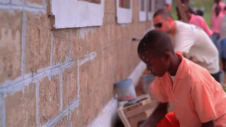 бисер : Painting the exterior of a school in a village in Kenya two hours north of the Africa city Mombassa. Стоковые видеозаписи