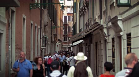 flanked : Slow motion shot of people walking down a narrow street,flanked on both sides by tall,old buildings. Shot with a high speed camera on May 2,2012 in Venice,Italy