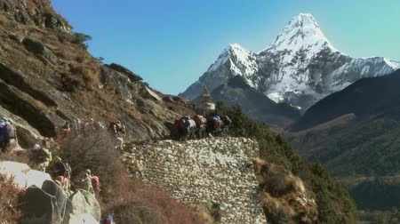 горный хребет : A long line of hikers and sherpas carry gear up the trail in the direction of Ama Dablam near a chorten monument.