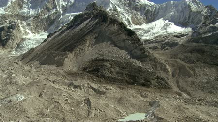 nuptse : Move from a prominent Himalayan peak to a dirty glacier flowing through a valley. Stock Footage
