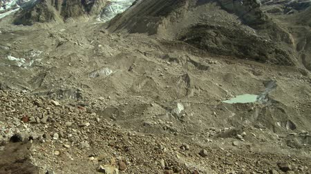 nuptse : Panorama of a dirty glacier flowing from the Himalayan mountains. A man is seen sitting on the rocky hillside at the beginning of the clip.