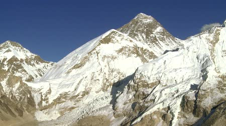 montar : A panoramic shot showing Mount Everest and nearby peaks Lhotse and Nuptse. A bird is seen flying.