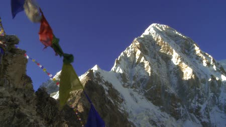 kamp : Buddhist prayer flags on a rocky ridge flapping in the wind. A sunlit Mount Everest is in the background.