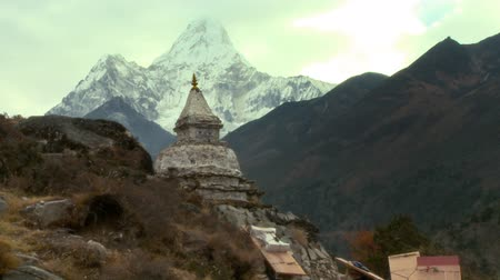 východní : People climbing up a trail carrying large boxes near an ancient building. A Himalayan peak perhaps Ama Dablam is in the background.
