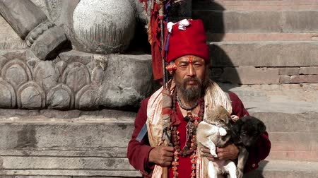 samsara : Old Nepali man holding puppies sits on stone steps in Nepal