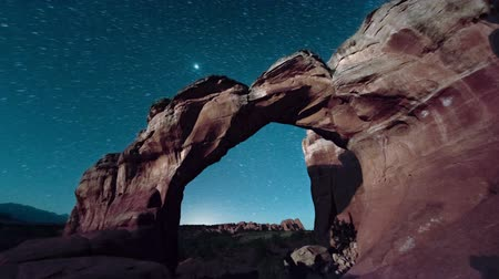 shadows : Stationary timelapse of sunrise in a canyon. Starts when the stars are out and then gets brighter. Cliff in the foreground. Stock Footage