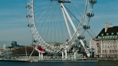 szórakoztatás : Time-lapse shot of the London Eye rotating above the Thames. People bustle by in the right corner as boats traverse the water. Filmed in October 2011. Cropped. Stock mozgókép