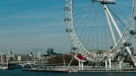 traverse : Time-lapse shot of the London Eye rotating above the Thames. People bustle by in the right corner as boats traverse the water. Filmed in October 2011. Panning shot. Stock Footage