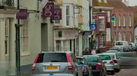 sul : Timelapse shot of a street in Rye. The shot shows pedestrians, traffic, parked cars and buildings during daytime. Panning shot. Vídeos