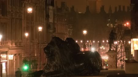 kolumna : Time-lapse shot from Trafalgar Square showing Big Ben at night. Lion statues at Nelsons column are in the foreground. Cars and double-decker busses on the street are blurred. Filmed in October 2011. Panning shot. Wideo