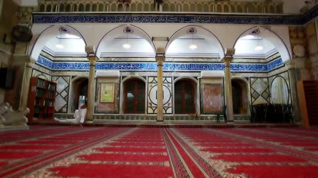 akko : Dolly left to right of the southern portion of the interior of the Jezzar Pasha Mosque in Acre, Israel. There is a man in white clothes sitting, leaning against a pillar, facing a bookshelf. 02192011 Stock Footage