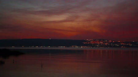 beach panorama : Slider dolly shot left to right of the lights of Tiberius, Israel at night across the Sea Of Galilee. Stock Footage