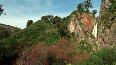 Pan of a wide shot of the top of the Iyon Tanur waterfall near Metula, Israel, near the Lebanese border. Also shown is a high mountain gorge carved out by the fall. The fall is surrounded by green and orange forest foliage.