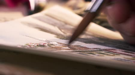 ilustração e pintura : Shot of an artist painting in details in a watercolor painting. Shot in Venice, Italy. Stock Footage