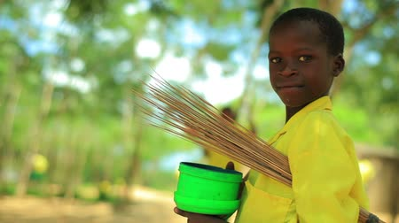 africký : Little boy carrying some straw and a bucket. looks at the camera and smiles. Dostupné videozáznamy
