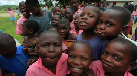 humanidade : Kids swarm around the camera in Africa Stock Footage