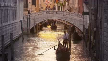veneza : Shot of a gondola in a canal with a bridge behind. Shot in Venice,Italy