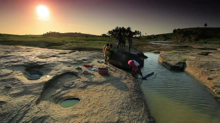 sul : Kids wash clothes in river under sunset in Africa Vídeos