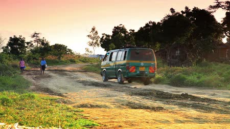 falu : Green van drives by on dirt road near village in Africa