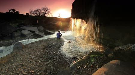 descobrir : Child watching a waterfall and tossing a rock at sunset in Kenya, Africa.