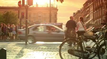 kodaň : Static shot of pedestrians about to cross a busy streeet in Copenhagen, Denmark. The shot was taken at sunset and a man and a woman are seen kissing in the foreground. Dostupné videozáznamy
