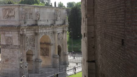 costantino : View of the Arch of Constantine from the Colosseum. The bricked facade of the Colosseum can be seen in the shot as tourists walk around the base of the Arch.