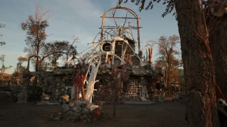 mennydörgés : Move from behind a tree showing the interesting structure at Thunder Mountain park in Imlay, Nevada. There is a statue of a Native American as well as a white framework of concrete tubes on the roof. There is also a doll in a skull on one of the foregroun