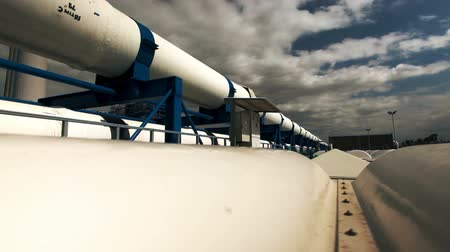 rurociąg : Wide dolly reveal of the lengthy white pipes running along the roof of a building at the IDE Ashkelon desalination plant in Israel, with billowing clouds and blue sky. Wideo