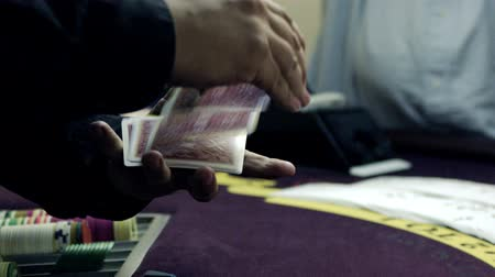 рукав : Dealer fanning and shuffling the cards over a purple table.