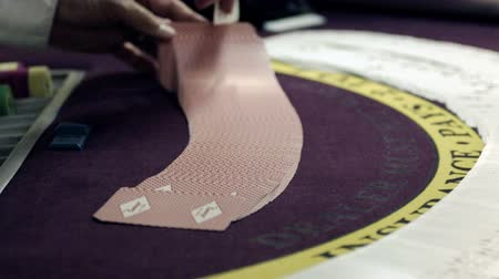 рукав : Shuffling card trick on a purple table.