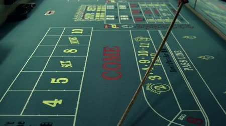 benefício : Moving dice across a craps table with the craps stick.