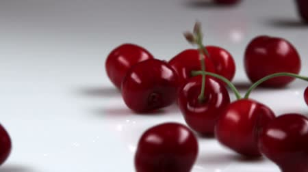 comestíveis : Red cherries falling onto table. Stock Footage